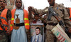 A fighter stands guard before a portrait of Hussein Badreddin Al-Houthi, the founder of Ansar Allah (aka the Houthi movement), during a rally in Sanaa on Sept. 14, 2020. (AFP/File Photo)