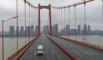 In this Jan. 25, 2020, file photo, an ambulance drives across a nearly empty bridge in Wuhan, China, after the city was placed under a 76-day lockdown amid a rising COVID-19 outbreak. China managed to place the contagion under control early while other countries continue to suffer from the pandemic one year after. (Chinatopix via AP, File)
