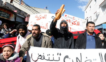 Demonstrators carry signs during an anti-government protest in Tunis , Tunisia January 26, 2021. (Reuters)