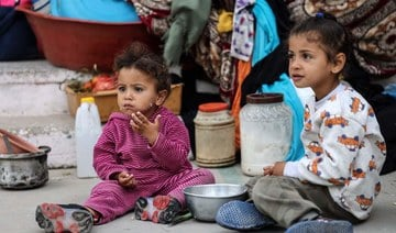 Palestinan children eat as families took shelter at a United Nations (UN) school in Rafah in the southern Gaza Strip on May 17, 2021. (AFP)