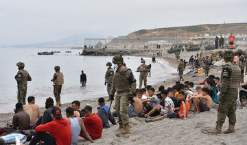 Migrants, including minors, who arrived swimming at the Spanish enclave of Ceuta, rest as Spanish soldiers stand guard on May 18, 2021 in Ceuta. (AFP)