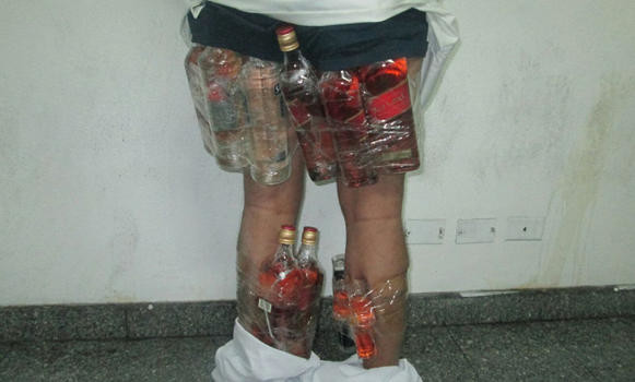 Smuggler caught with bottles of liquor taped to his legs