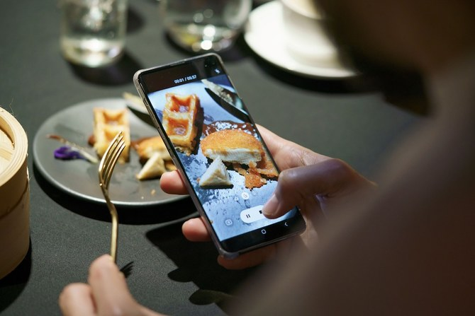 A guest uses a mobile phone to take a video of a meal featuring a nugget made from lab-grown chicken meat during a media presentation in Singapore, the first country to allow the sale of meat created without slaughtering any animals, on December 22, 2020. (AFP/File Photo)