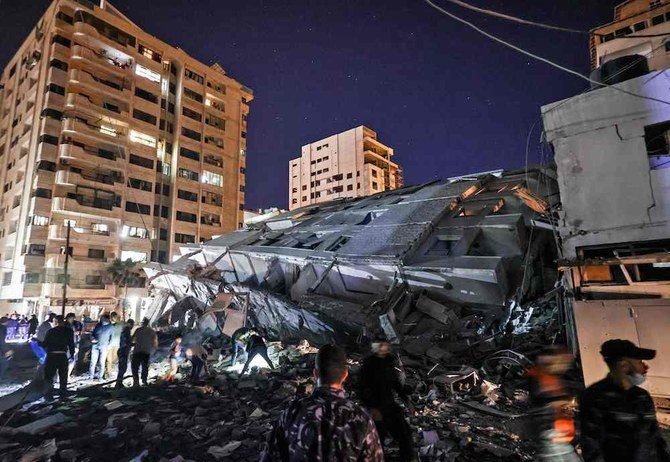People gather at the site of a collapsed building in the aftermath of Israeli air strikes on Gaza City on May 11, 2021. (AFP)